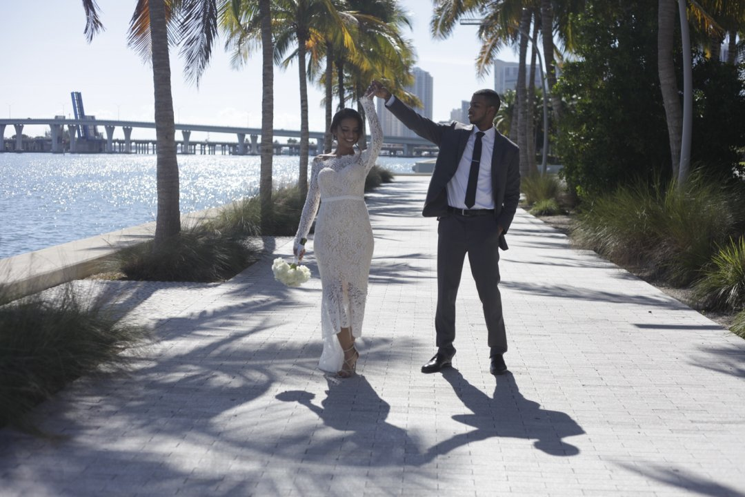 Bride and groom walking along the water in California