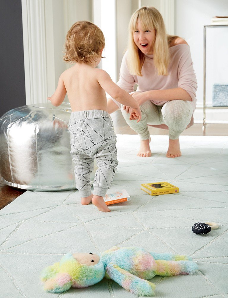 A baby runs towards his mother in a playroom with toys.