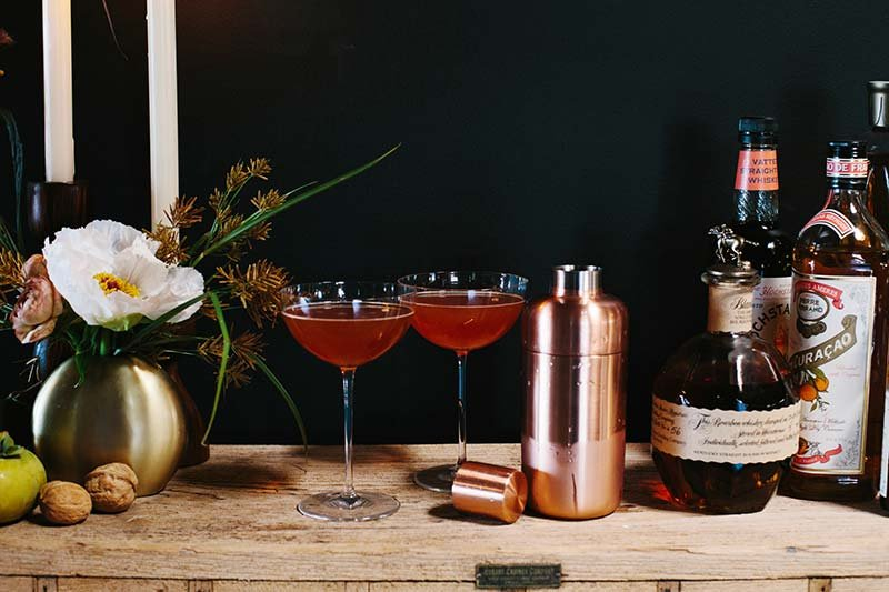 Red cocktails in cordial glasses next to a copper cocktail shaker and bottles of alcohol and cocktail ingredients