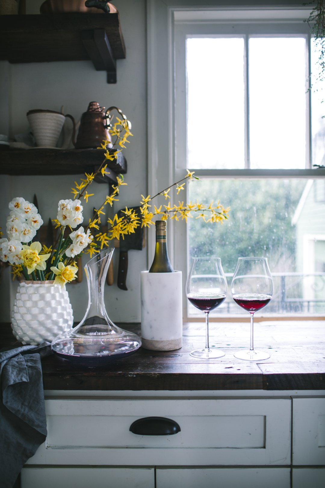 Vase with big bouquet of yellow spring flowers, wine carafe, wine in wine cooler, and wine glasses filled with red wine on countertop