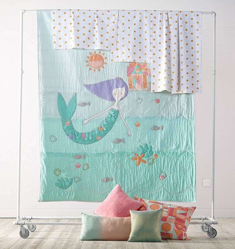 Mermaid bedding is displayed with a quilt, pillows and sheets.