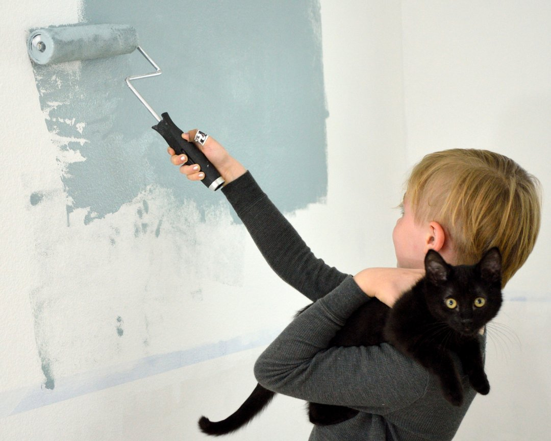 Child applying blue paint to wall with paint roller