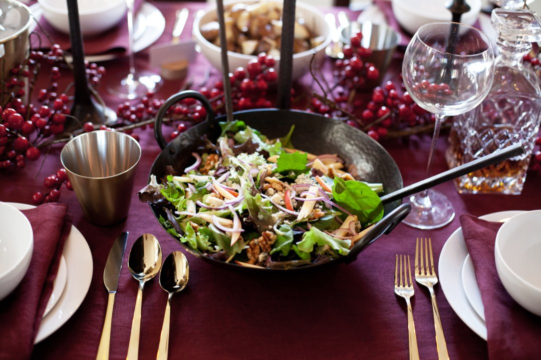 Leafy green salad with walnuts and apple and red onion slices in a hammered iron serving bowl