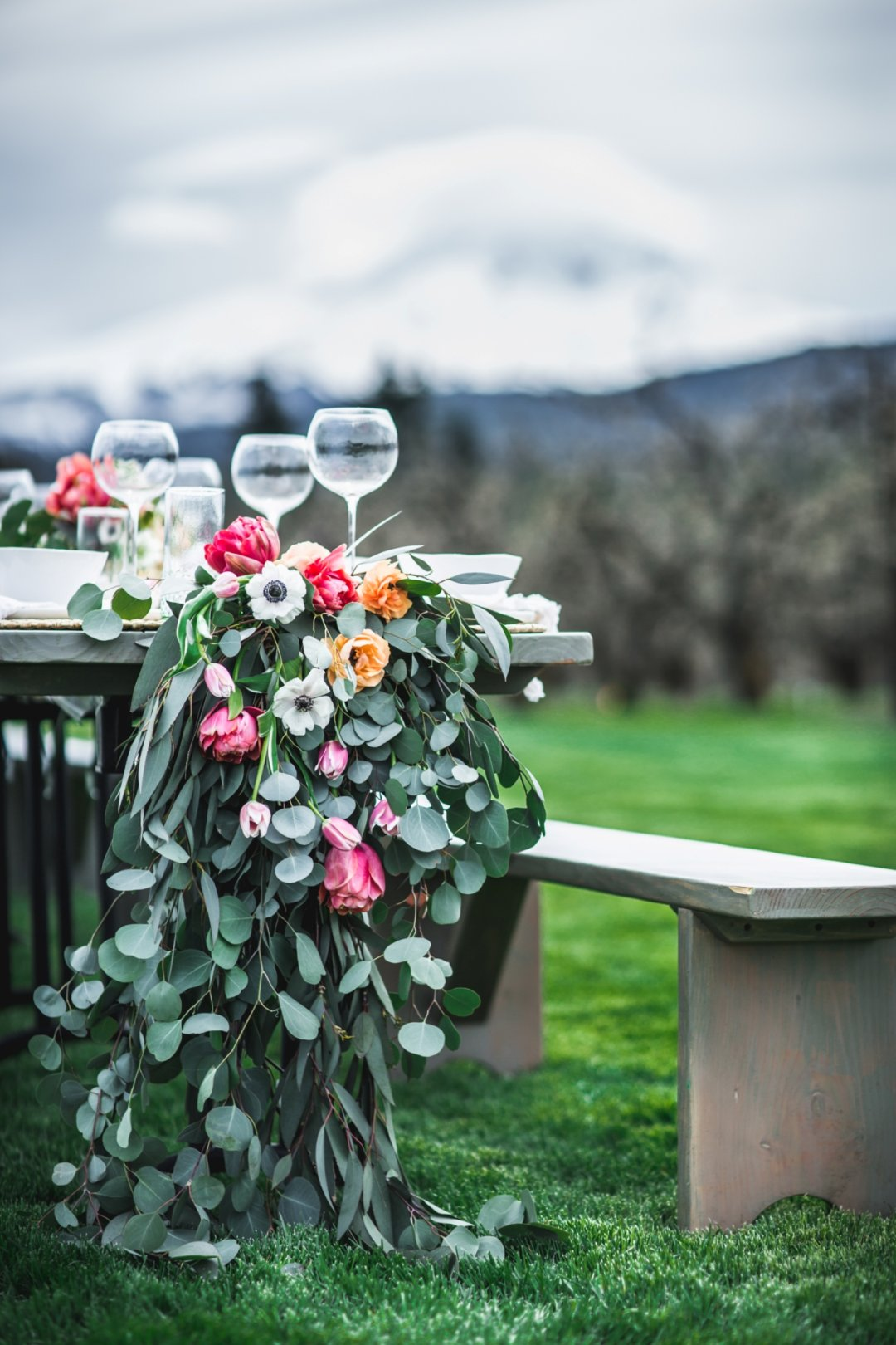 Side view of table with wreath of flowers flowing down and mountains in background