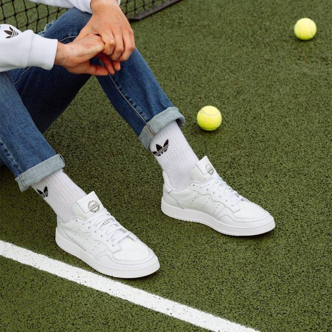adidas Supercourt on feet con vaqueros