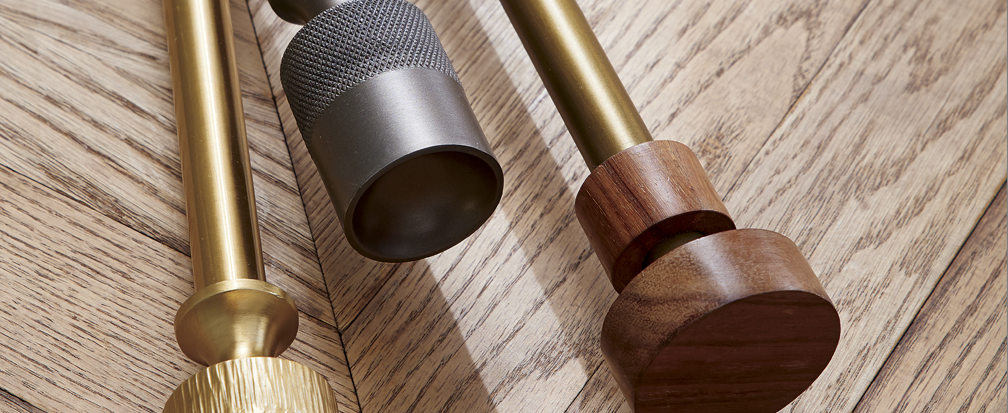 Gold, black and bronze curtain rods next to a wood background