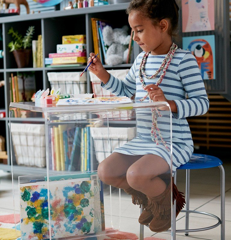 A small, arylic desk offers a toddler a place to learn to paint