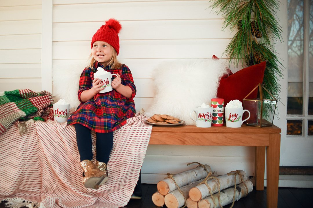 Little kid drinking hot chocolate from Christmas mugs and eating cookies on bench on front porch