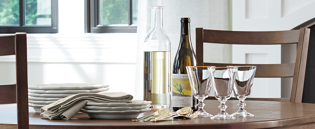 French wine glasses, wine, and plates for a dinner party