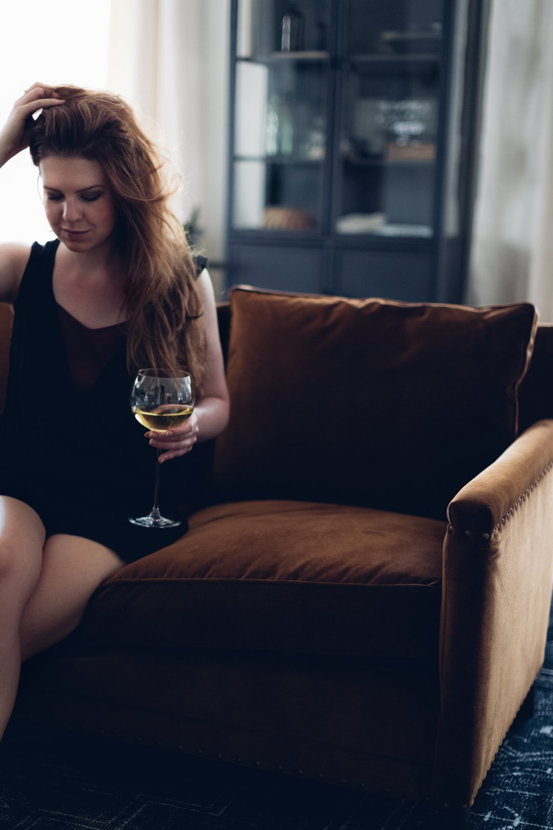 Woman sitting on sofa with glass of white wine