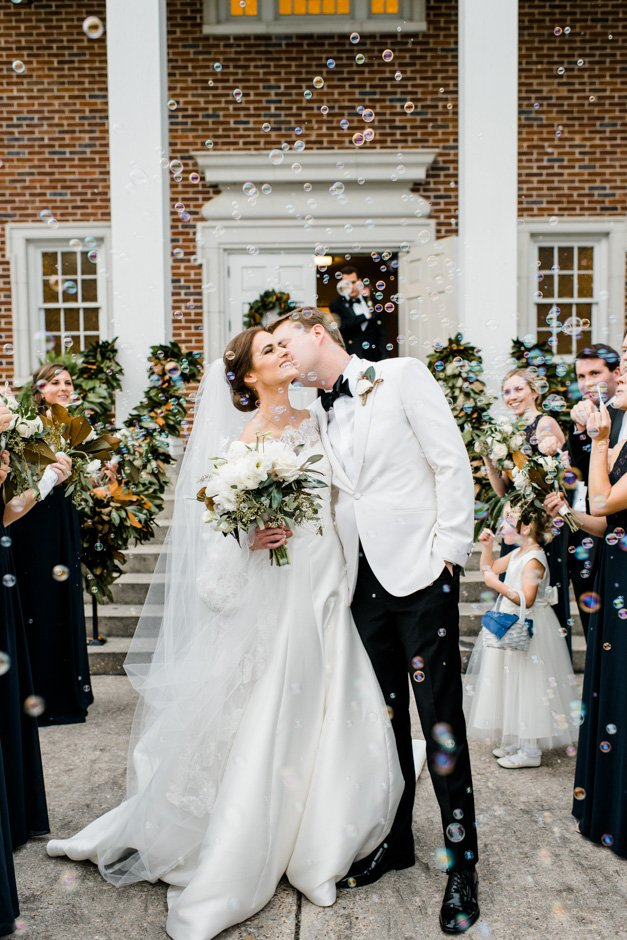 Bride and groom leave church as guests blow bubbles