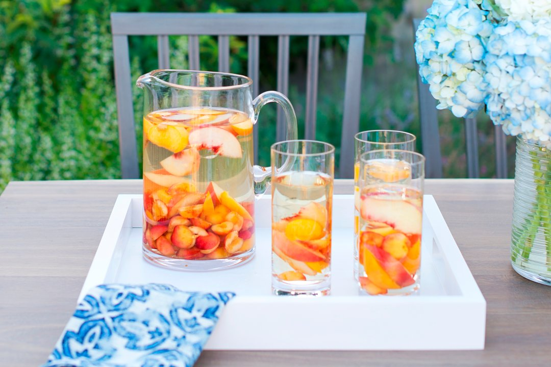Sangria with peaches and yellow cherries in pitcher and glasses on white tray