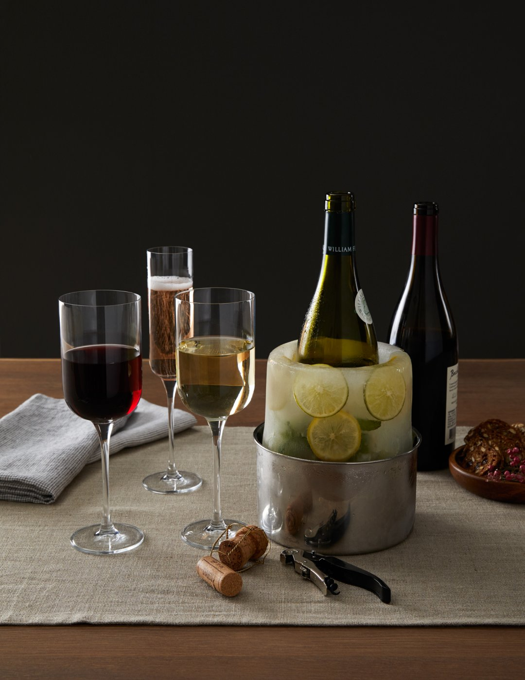Glasses of red and white wine next to a wine bottle in an ice mold