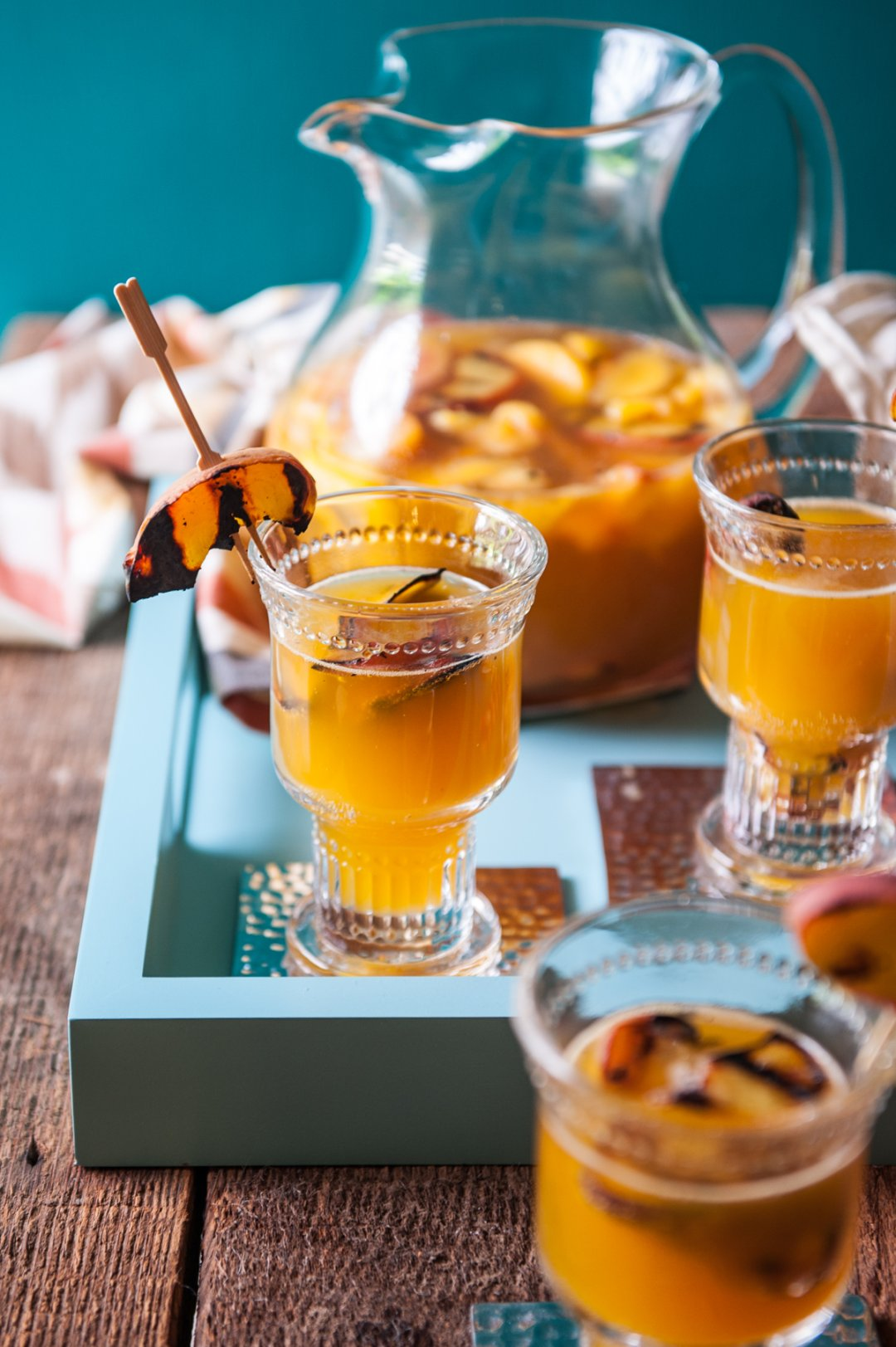Fruity sangria with grilled peach skewers on blue serving tray