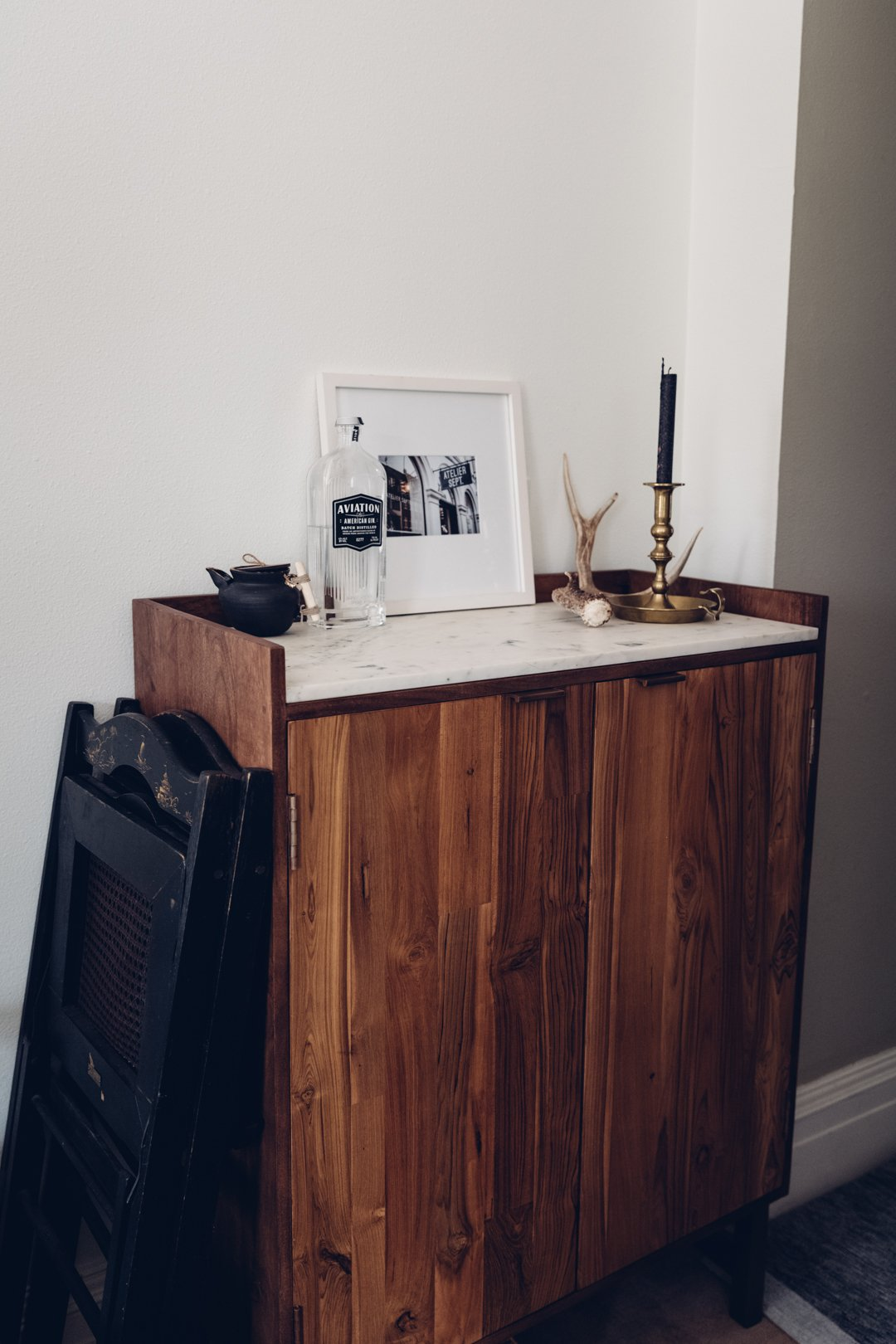 Wood and marble Cantina bar cabinet with antler and candle accents