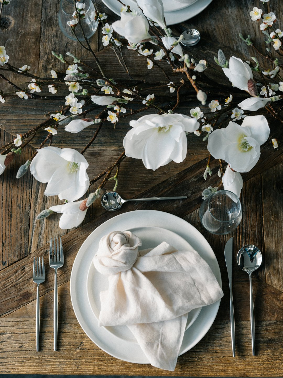 a table set for two with white flowers and branches displayed in the middle