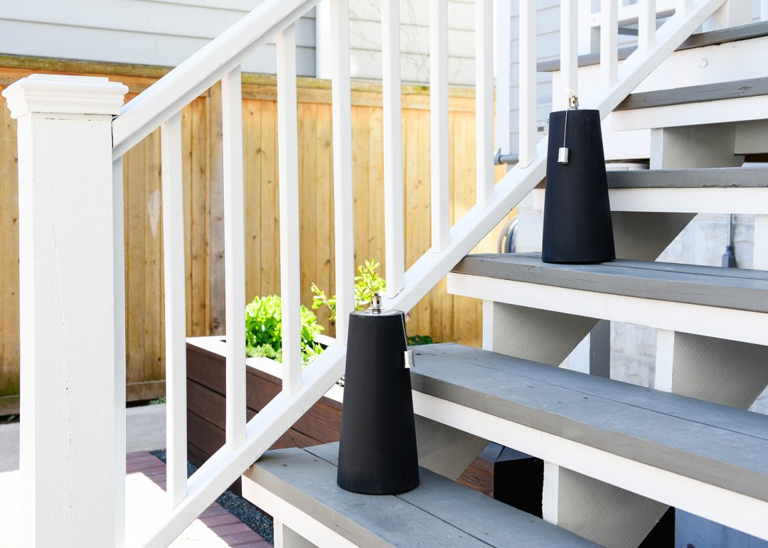 Two black oil lamps on outdoor staircase