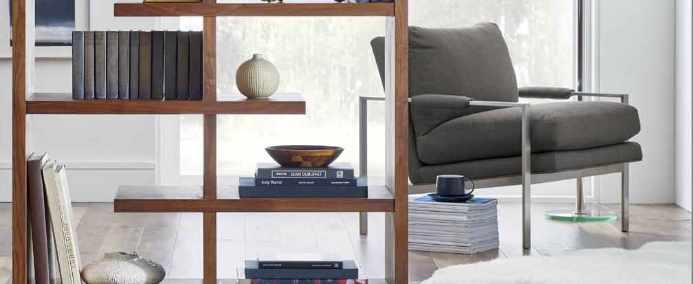 Plush armchair and wooden bookcase with books and vases next to large window