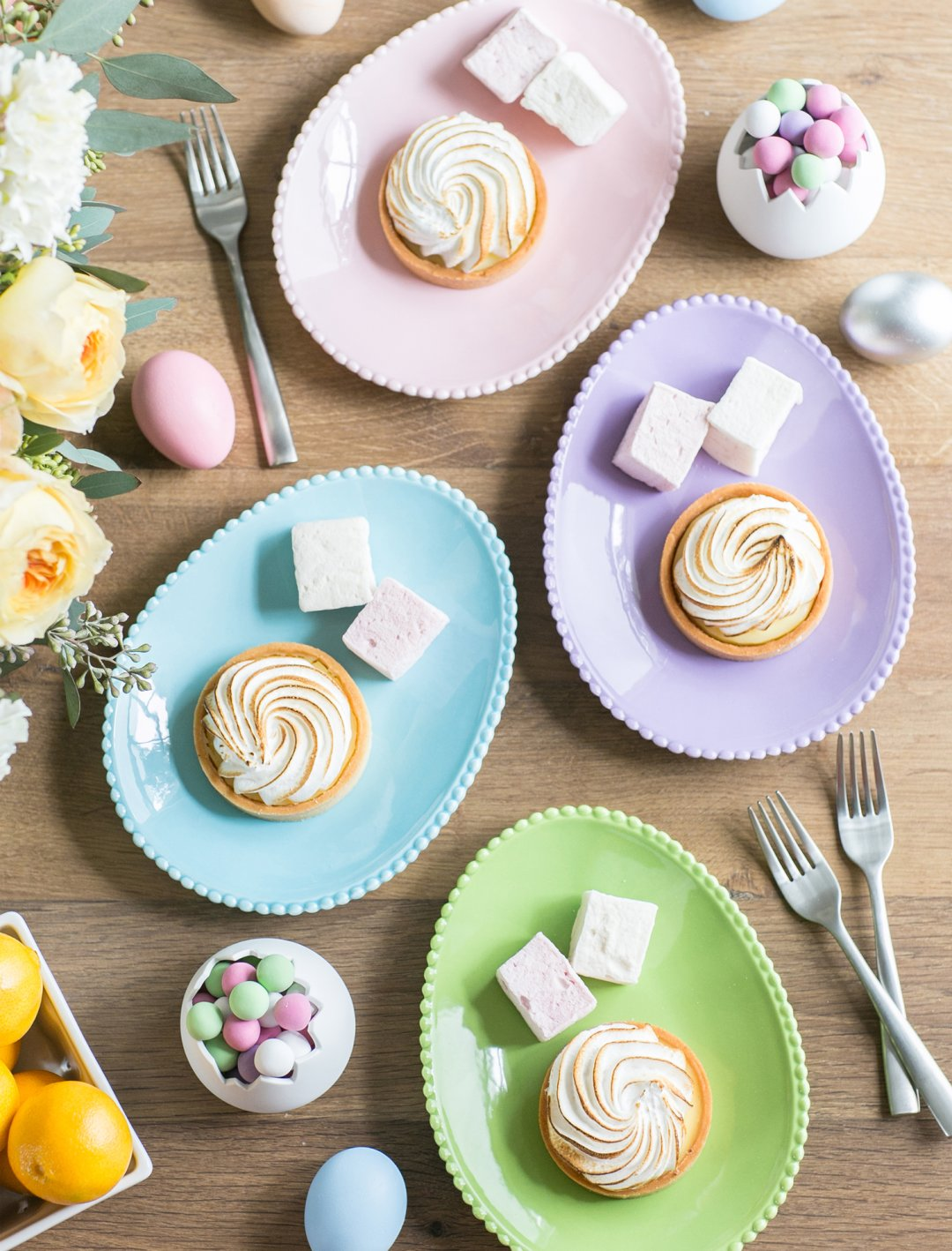 Pastel colored Easter egg appetizer plates with desserts