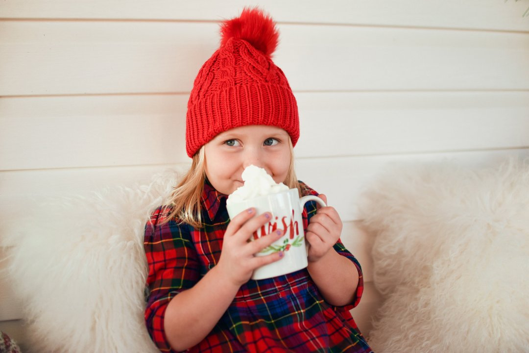 Little kid in red hat and flannel drinking hot chocolate with whipped cream from a holiday-themed mug