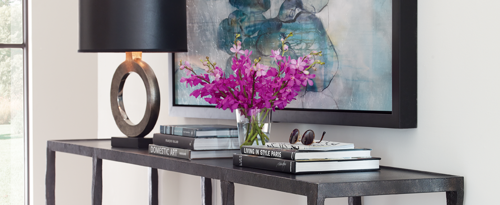 Lamp, magazines and a vase of purple flowers on top of a steel entryway table
