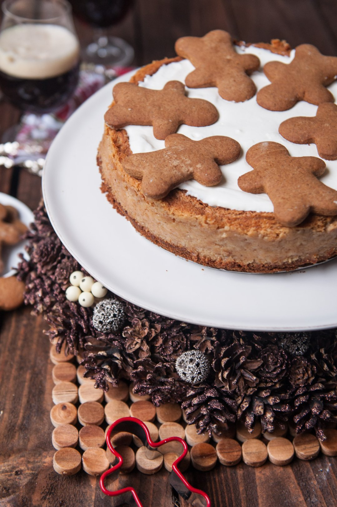 Gingerbread cheesecake on white cake server set atop a holiday-themed display of shimmery pine cones