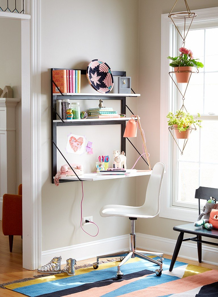 A wall mounted desk turns a corner into a kids study room.