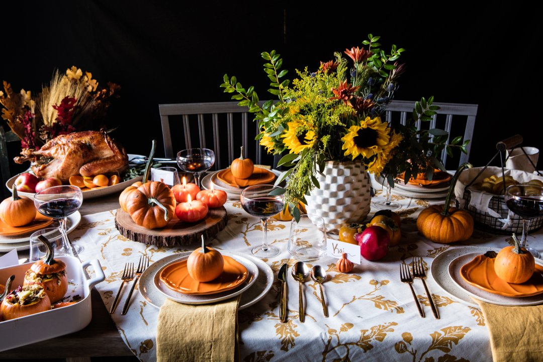 Thanksgiving table decorated with real mini pumpkins, pumpkin candles, and set with orange pumpkin plates