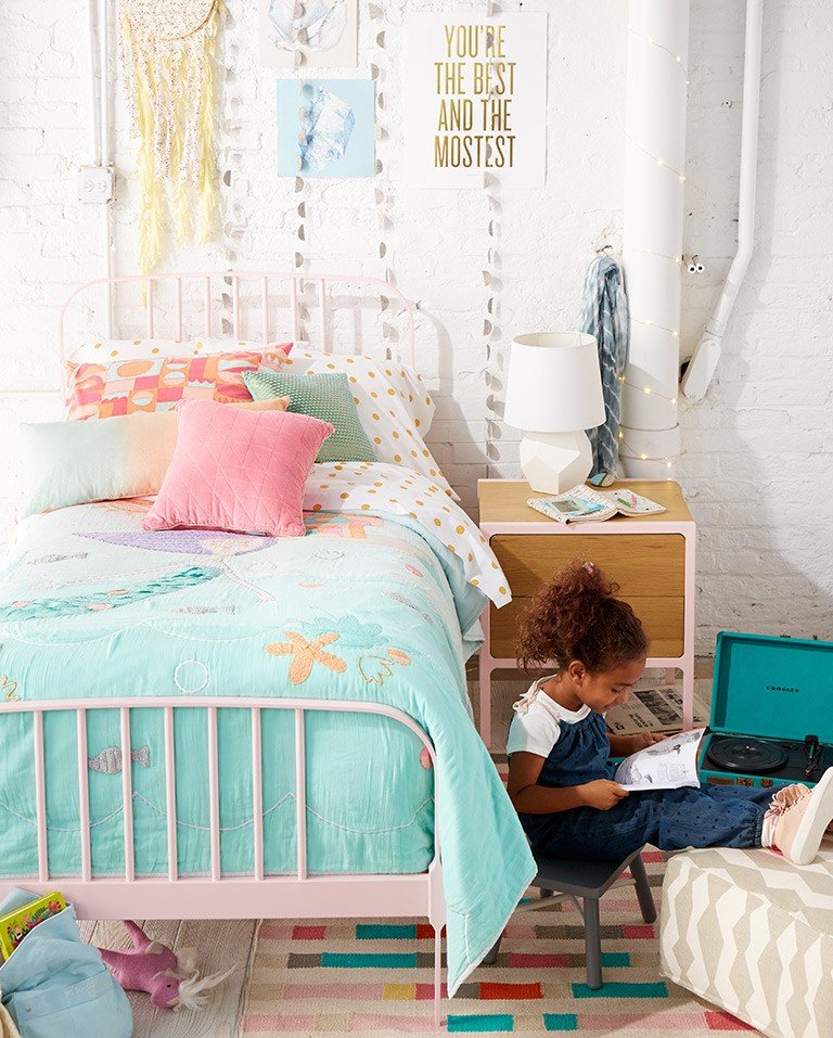 A little girl plays in a whimsical mermaid themed bedroom filled with decorations.