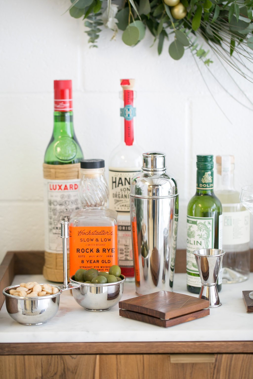 bar cart topped with bottles of alcohol and a drink mixer