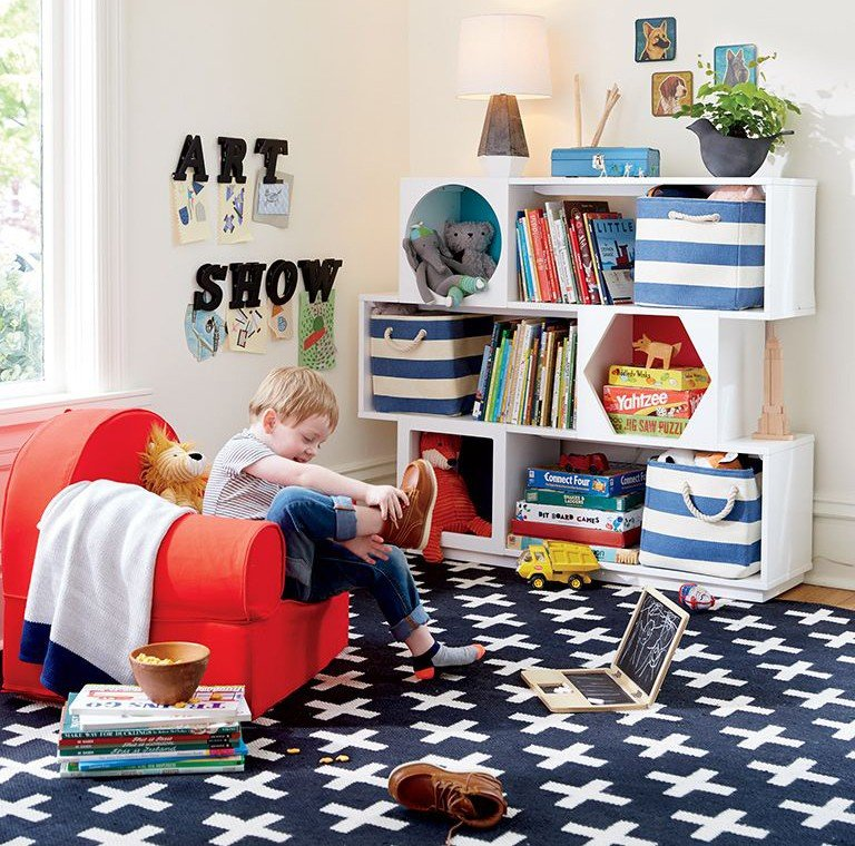 A young boy reads a book in his playroom.