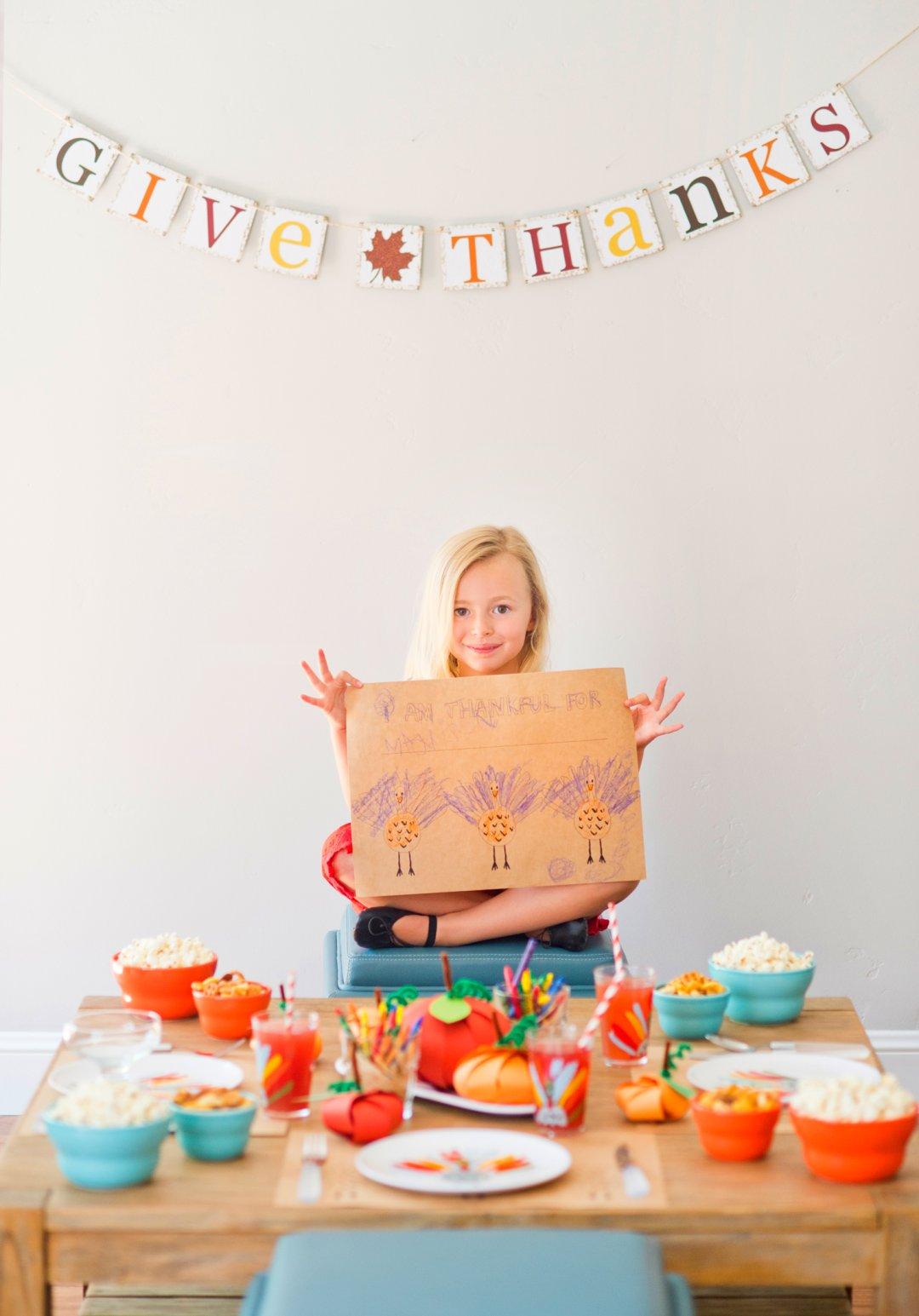 Girl holding handmade Thanksgiving turkey artwork behind a small kids dinner table