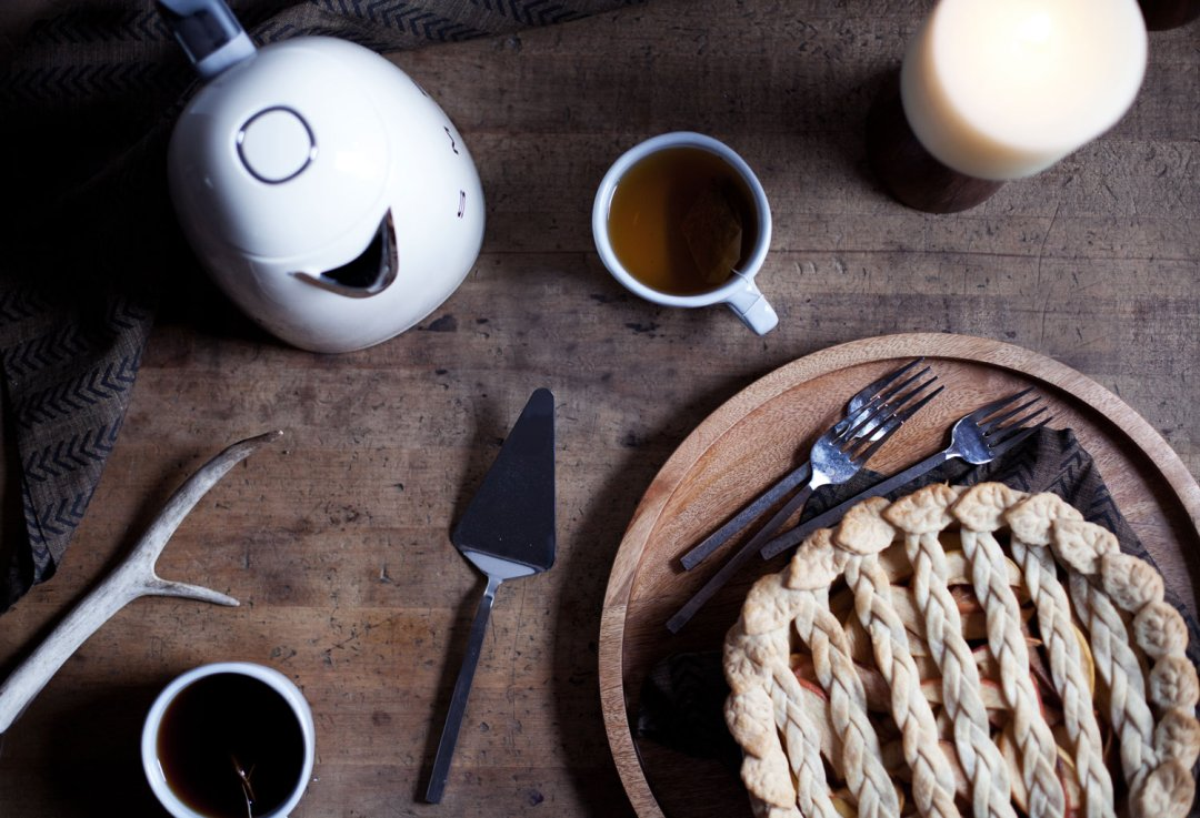 Baked and browned pie on a wood serving platter next to flatware and two cups of tea