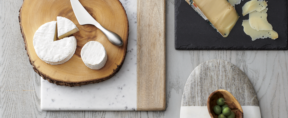 Cheese wheels and slices on wood and marble cheese boards with knives