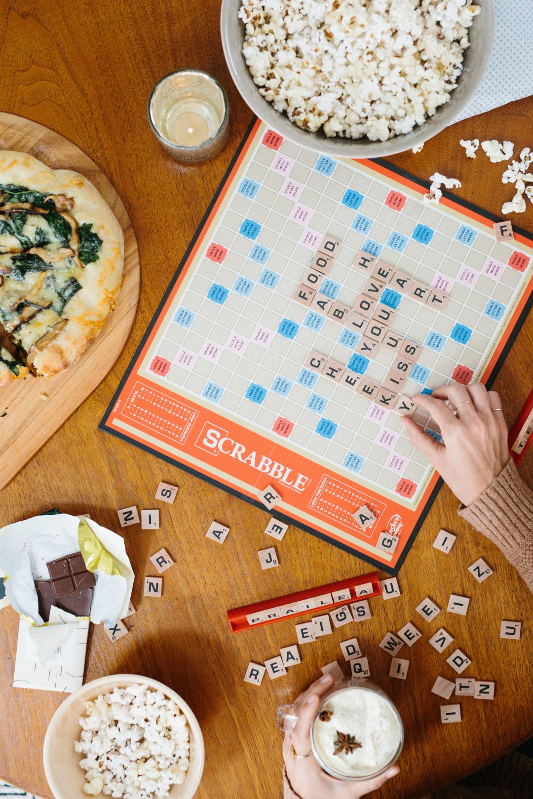 Scrabble game board and letter squares surrounded by bowls of popcorn on a wood coffee table