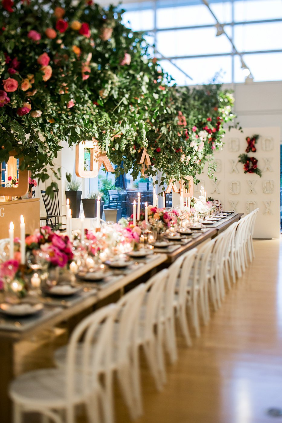 Line of white chairs by Valentine's Day table