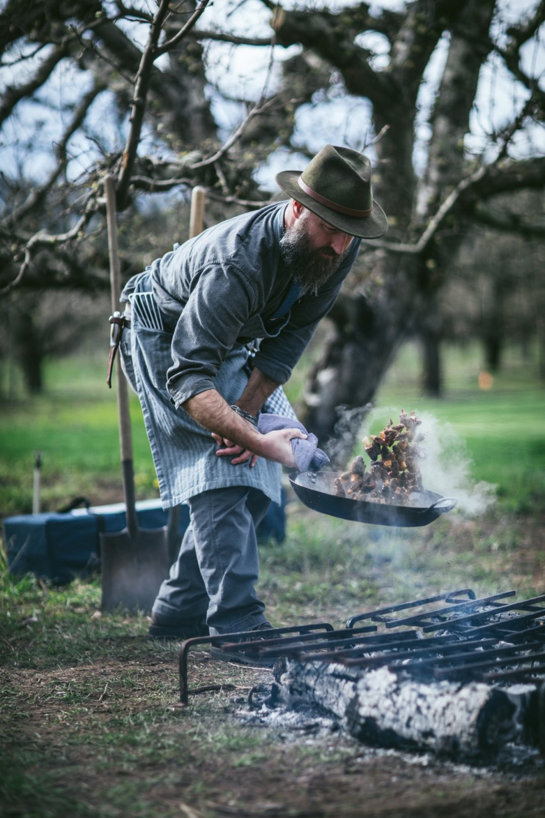 Man flipping food in a skillet over grill in ground