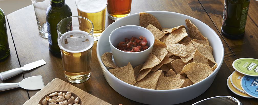 Game day party with chips and salsa, peanuts and beer