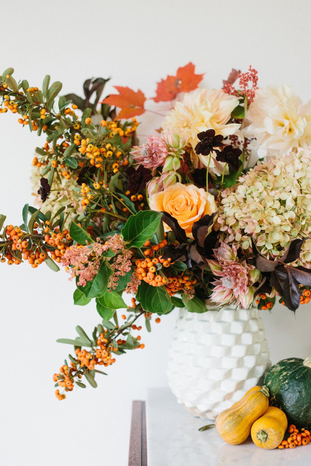Floral bouquet in rustic fall colors including orange and yellow in a white vase