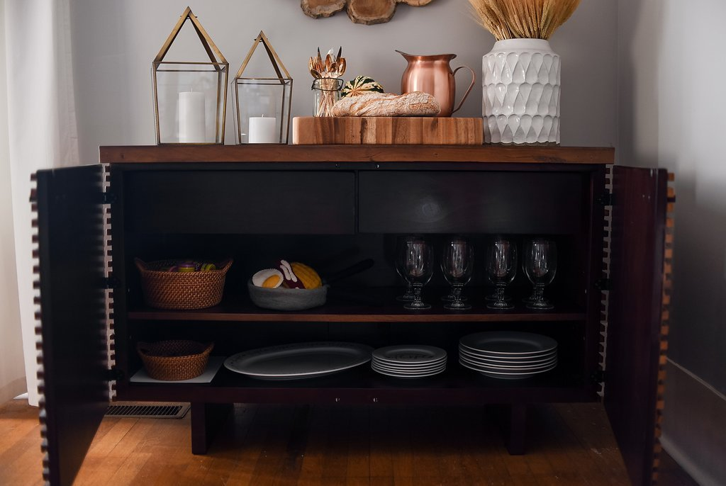 Dinnerware, glassware and flatware organized inside the sideboard cabinets