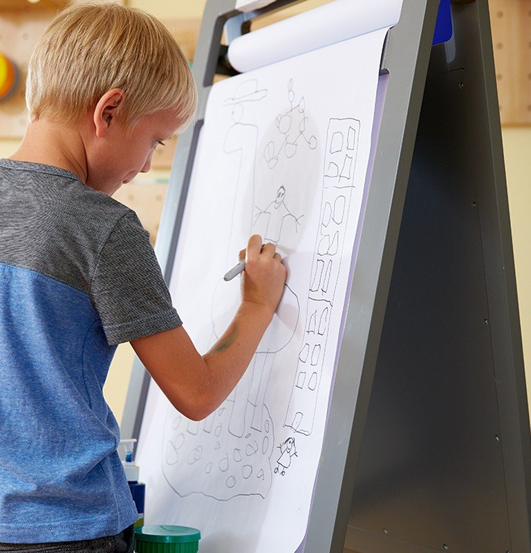 A young boy draws at an easel