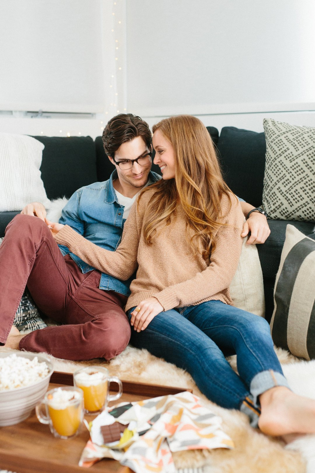 Couple in cozy living room behind a serving tray of popcorn and frothy cocktails