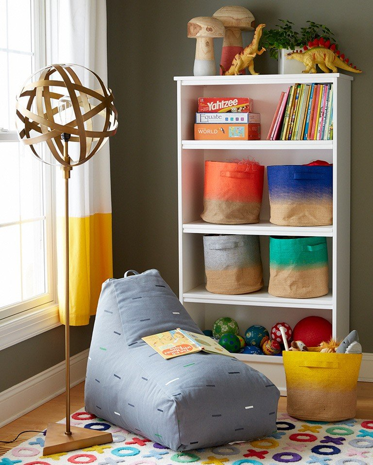 A beanbag makes a cozy place to read next to a bookcase and lamp.