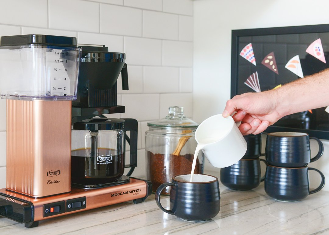 Pouring coffee into black mug with copper coffee maker in background
