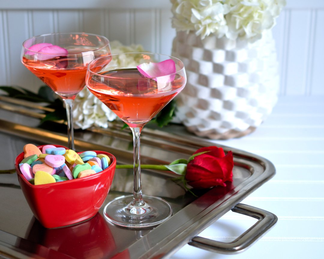 Pink Valentine's Day cocktail on a silver tray with red heart bowl
