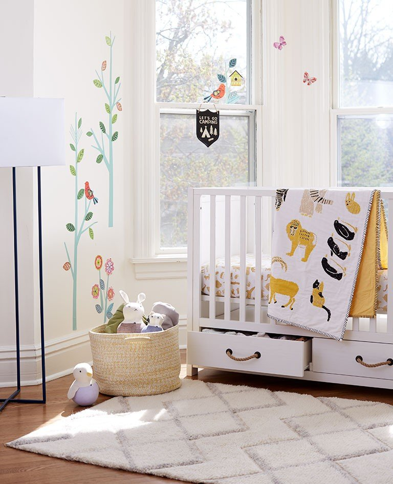A nursery decorated with a stoage crib with drawers.