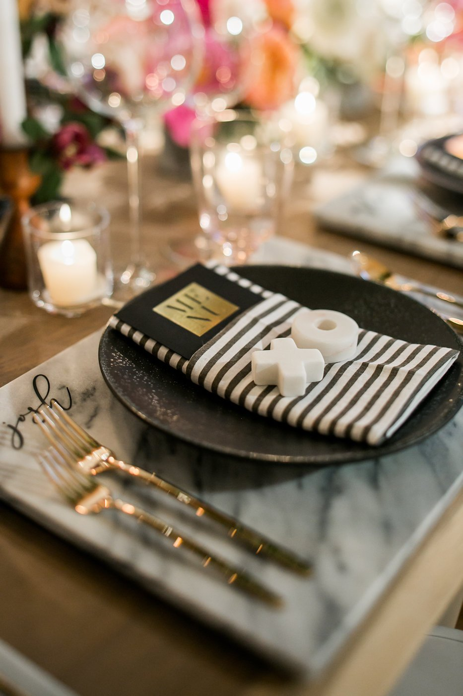 Table setting with black dinner plate and striped napkin