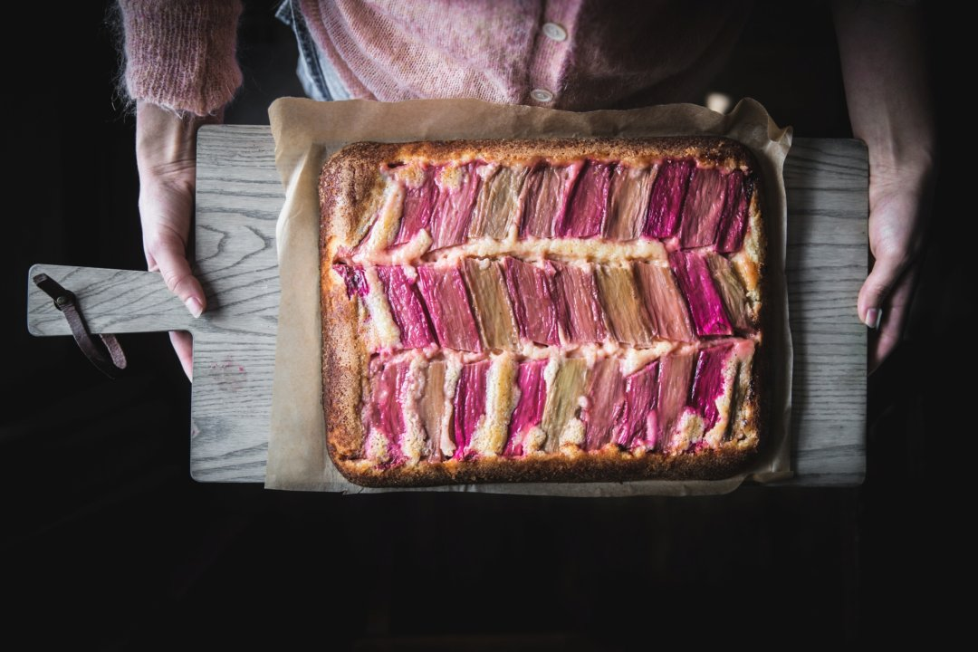 Woman holding rhubarb tart on serving board