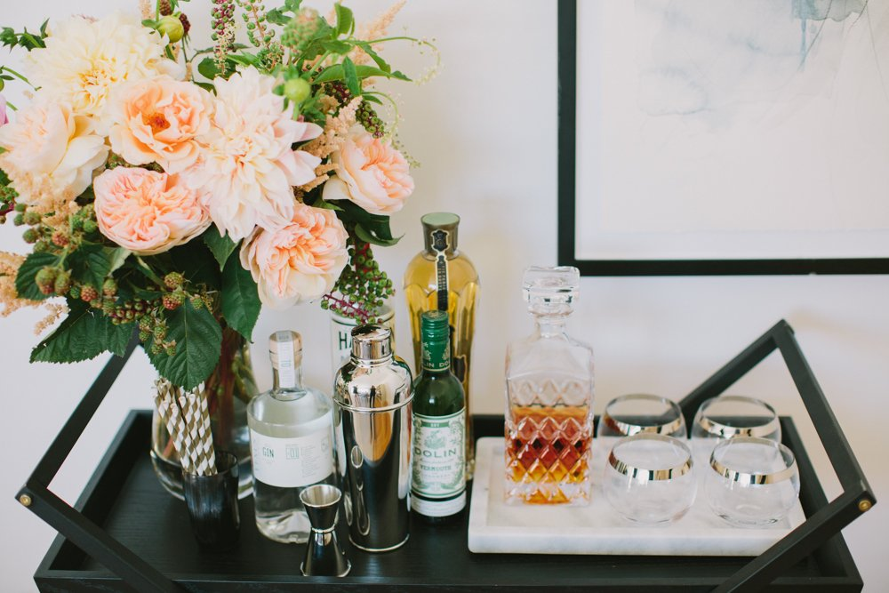Stocked barcart stocked with alcohol, shakers, jiggers and drinking glasses and decorated with flowers