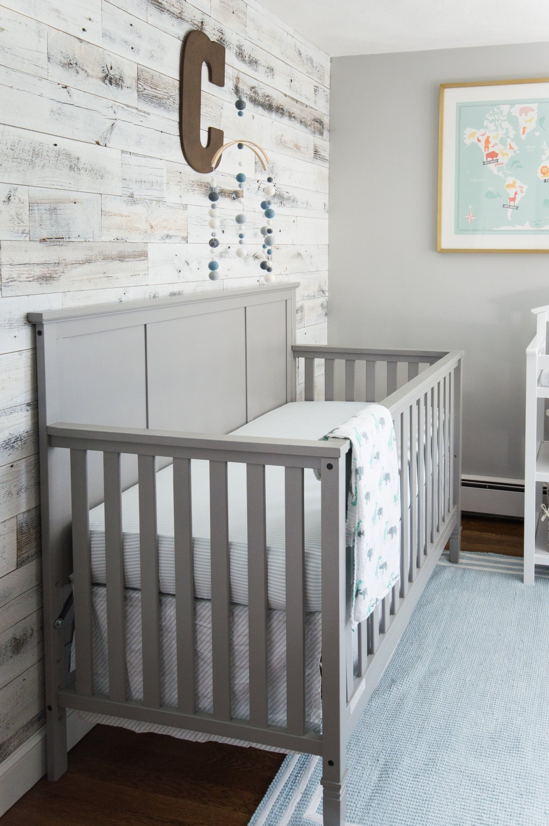 Reclaimed wood accent wall in baby boy nursery